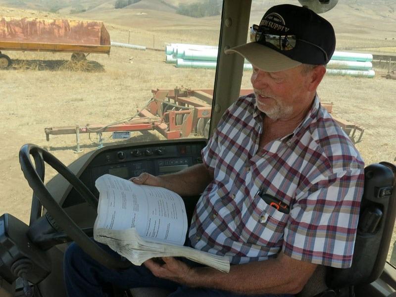 Dave Alford studiază codul de programare pentru a înțelege de ce nu funcționează tractorul // FOTO: npr.org